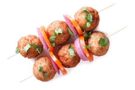 Roasted meatballs on skewers with fresh vegetables isolated on white background. horizontal view from above photo