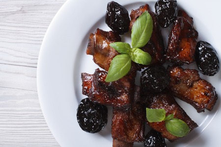 Pork ribs stewed with prunes on a plate. horizontal view from above closeup photo