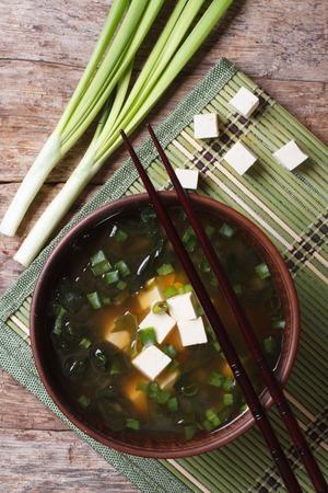Japanische Miso-Suppe in einer braunen Schüssel auf den Tisch. vertikale Ansicht von oben Lizenzfreie Bilder