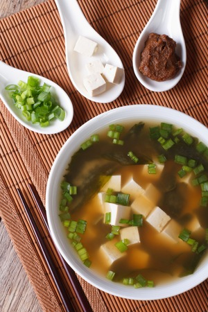 dashi: Japanese miso soup in a white bowl and ingredients in a spoon on a table close-up. vertical top view Stock Photo