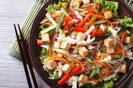 Japanese tofu salad with fresh vegetables close-up on a plate. horizontal top view