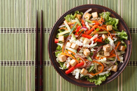 green cabbage: Asian salad with tofu and fresh vegetables close up on a plate. horizontal view from above Stock Photo