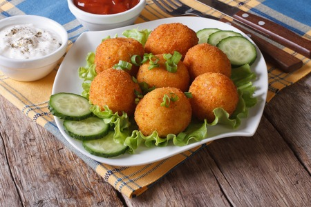 potato croquettes with lettuce and cucumber on a plate close-up. horizontal