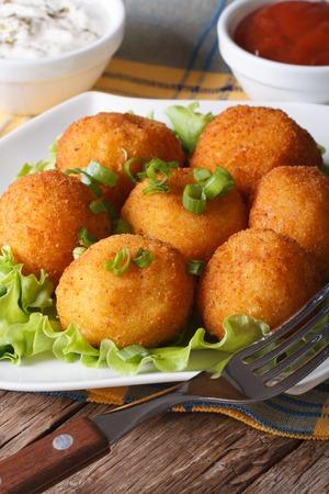 Delicious potato croquettes on a white plate close-up. vertical
