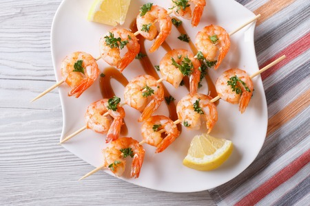 Grilled shrimp on skewers with lemon on a plate close-up. horizontal view from above photo