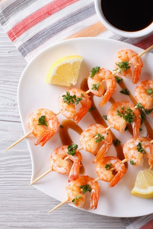 Grilled shrimp on skewers with lemon on a plate close-up. vertical top view photo