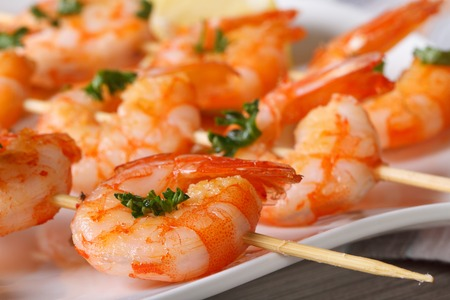 fried shrimp: Delicious grilled shrimp on wooden skewers on a plate macro. horizontal