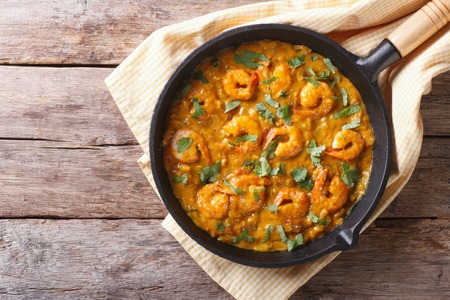 indian food: Shrimp in curry sauce in the pan. horizontal view from above