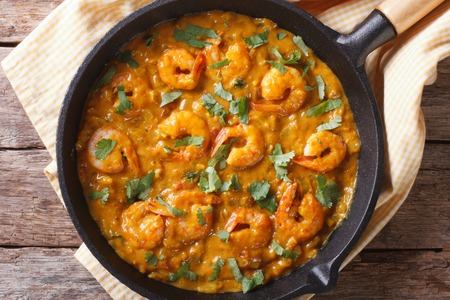 Shrimp in curry sauce in a pan close-up. horizontal view from above Archivio Fotografico