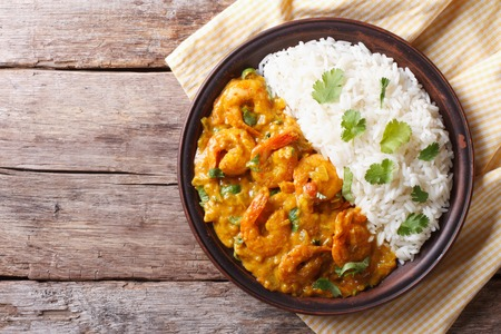Shrimps in curry sauce and rice on a plate. horizontal view from above
