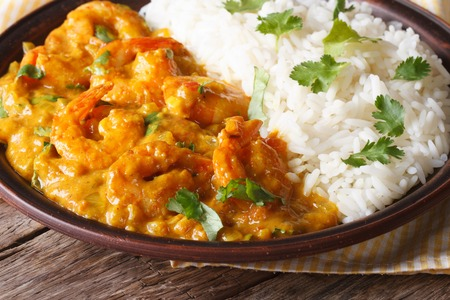 Shrimps in curry sauce with rice and cilantro closeup on a plate. horizontal