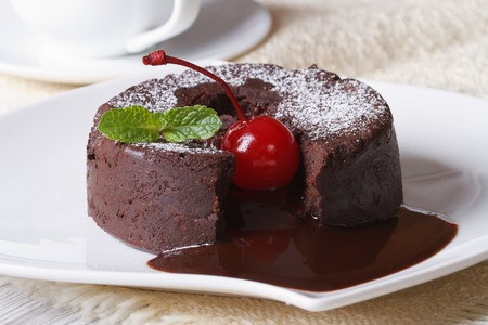 cakes background: fondant chocolate cake with cherries and mint close up on a plate and coffee. horizontal