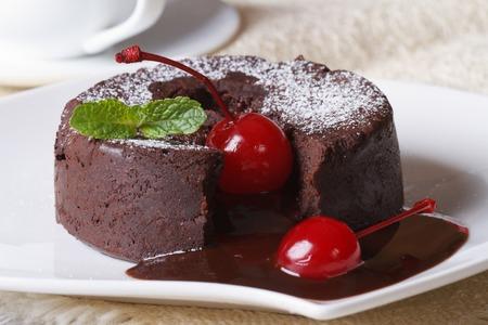 Fondant-Schokolade Kuchen mit Kirschen und Minze Makro auf einem Teller und Kaffee. Horizontal