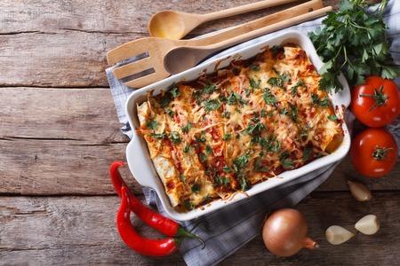 pollo: Enchilada mexicana en una fuente de horno con los ingredientes sobre la mesa. vista horizontal desde arriba