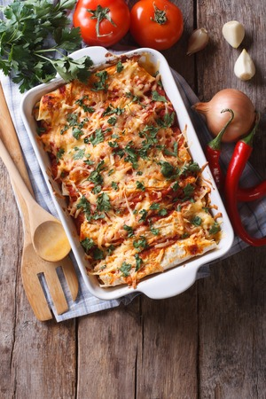 baked chicken: Mexican enchilada in a baking dish with the ingredients on the table. vertical view from above