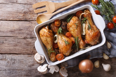 chicken leg: Baked chicken legs with mushrooms and vegetables. horizontal view from above