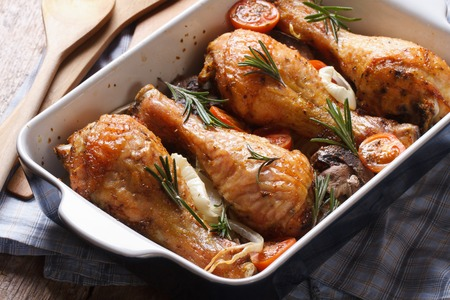 chicken legs with rosemary in a baking dish close-up on the table. horizontal
