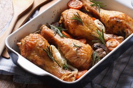aves de corral: piernas de pollo con romero en un plato para hornear de cerca en la mesa. horizontal