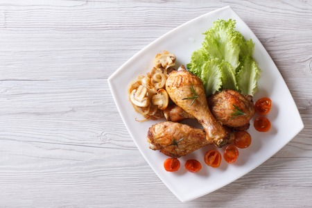 chicken meat: Fried chicken legs with mushrooms and tomatoes on a plate. horizontal view from above
