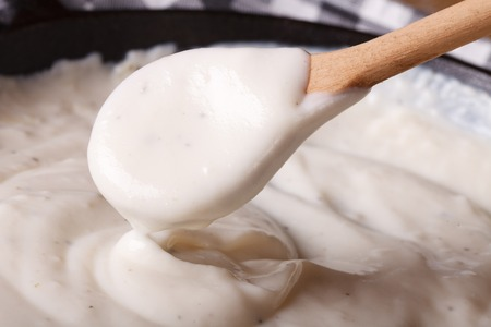 wooden spoon: bechamel sauce stirred a wooden spoon macro horizontal