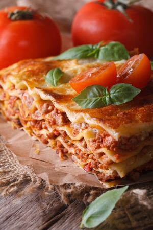 Italian lasagna with basil close-up on paper. vertical rustic style