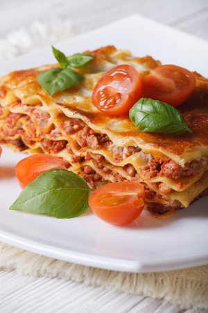 melted cheese: Portion of Italian lasagna with fresh basil and tomatoes on a white plate. vertical