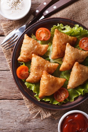 samosa: samosa on a plate with sauce and tomatoes closeup. vertical view from above, rustic style