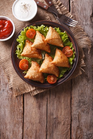 Indian samosa delicious pastry on a plate on a wooden table. vertical view above, rustic style photo