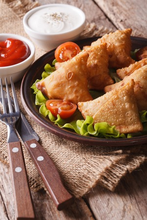 vegetarian samosas on a plate with tomatoes and lettuce on a wooden table. vertical photo