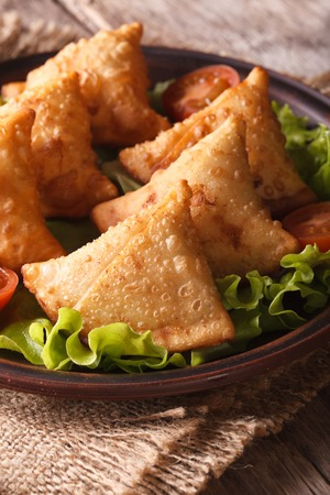 samosa: samosa on a plate with tomatoes and lettuce on a wooden table. Vertical close-up