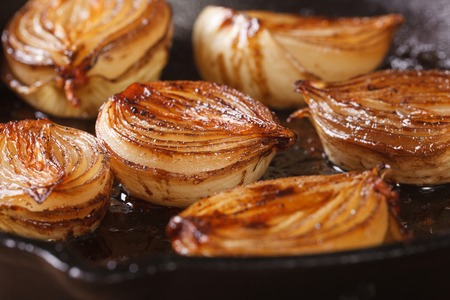 onion: ñaramelized onion halves with balsamic vinegar in a pan close-up, horizontal