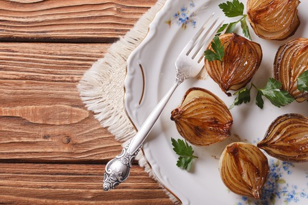 spanish onion: caramelized onions in balsamic vinegar on a white plate. horizontal view from above