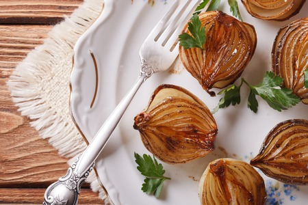 spanish onion: caramelized onions in balsamic vinegar on a white plate closeup. horizontal view from above