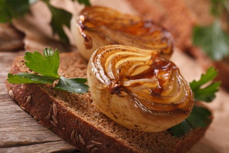 spanish onion: Open sandwich with caramelized onions and parsley macro on an old table, horizontal rustic style