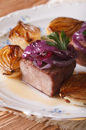 Beef grilled and caramelized onions on a white plate. vertical photo