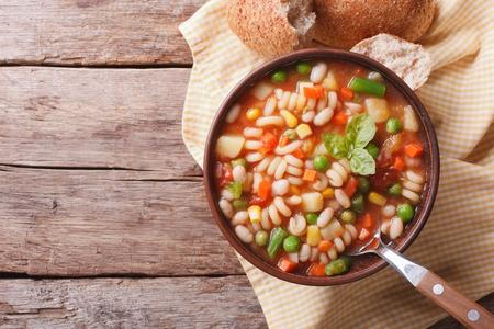 judias verdes: Sopa minestrone italiano y pan en la mesa. vista horizontal desde arriba