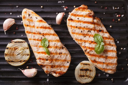 chicken breast: Grilled chicken with onion and garlic on the grill close up. horizontal view from above