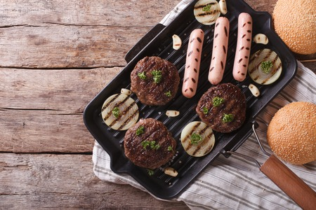 bbq party: Burgers and sausages on a grill pan. horizontal view from above