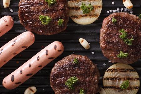 hamburguesa: hamburguesas y salchichas con verduras a la parrilla macro. vista horizontal desde arriba Foto de archivo