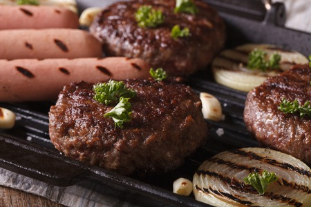 hotdog sandwiches: grilled burgers with vegetables in a pan grill closeup. horizontal Stock Photo