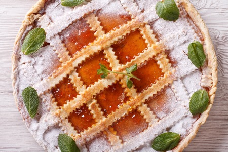 Italian crostata with apricot jam close up on the table. horizontall top view photo