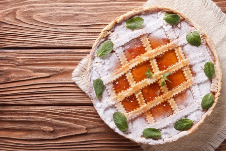 Tasty Italian tart with apricot jam and mint on a wooden table. horizontal view from above photo