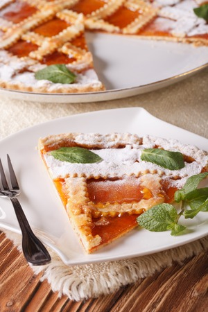 Slice of Italian tart with apricot jam on the table close-up. Vertical photo