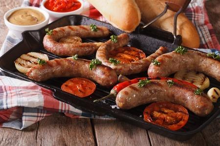 pepe nero: salsicce con verdure su una bistecchiera, il sugo e panini sul tavolo close-up. orizzontale
