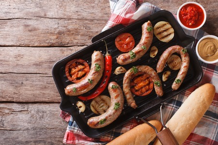 cooked sausage: sausages with vegetables on a grill pan on the table. horizontal view from above Stock Photo