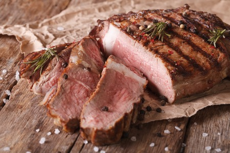 medium closeup: sliced beef steak medium on an old table. Horizontal close-up, rustic style Stock Photo