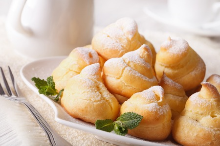 powdered: Profiteroles with powdered sugar close-up on a plate. horizontal Stock Photo
