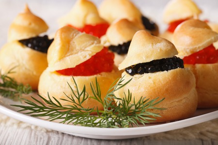 Finger food: profiteroles stuffed with red and black caviar on a plate close-up. horizontal photo