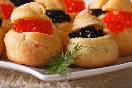 fresh food fish cake: Fresh profiteroles with red and black caviar on a plate macro. horizontal Stock Photo
