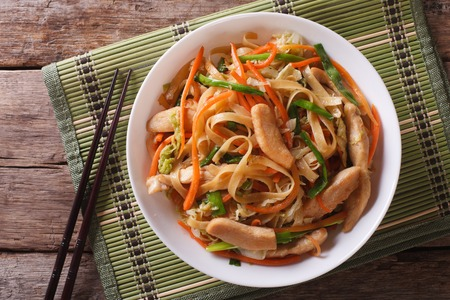 food dish: Chow Mein: fried noodles with chicken and vegetables close-up. horizontal view from above